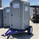 front view of portable toilet trailer in yard