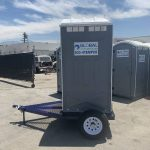 side view of portable toilet trailer in yard